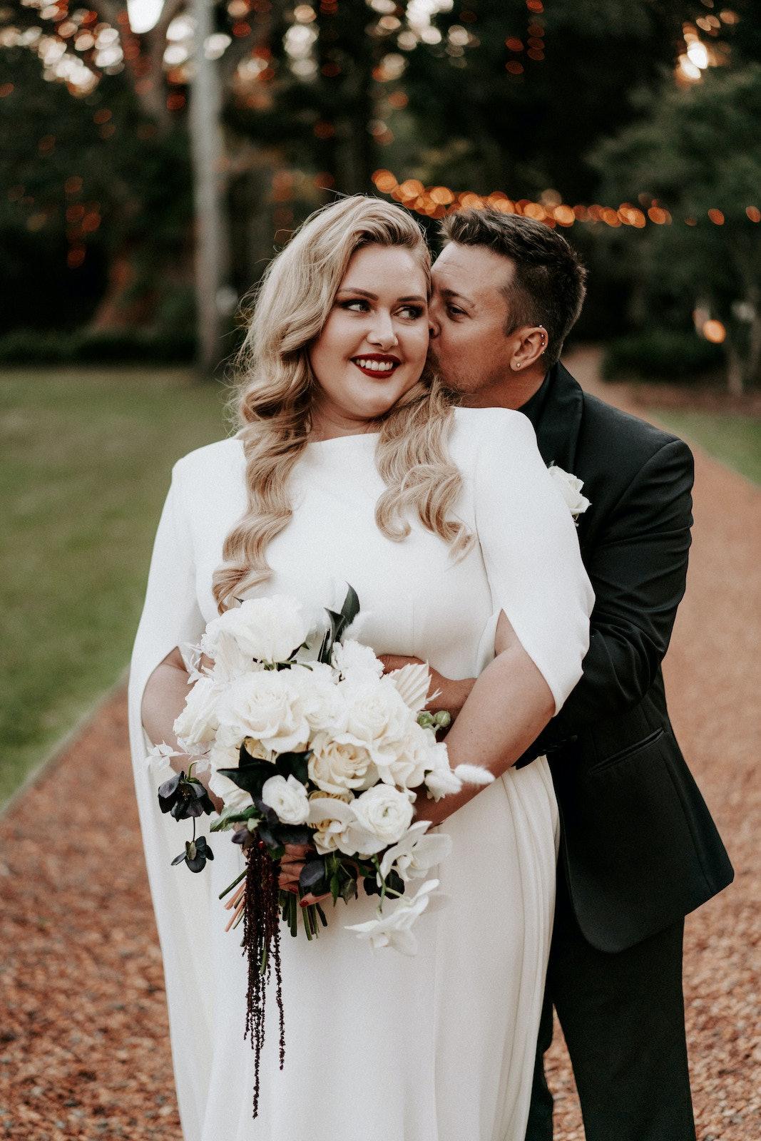 Groom standing behind bride kissing her on the cheek