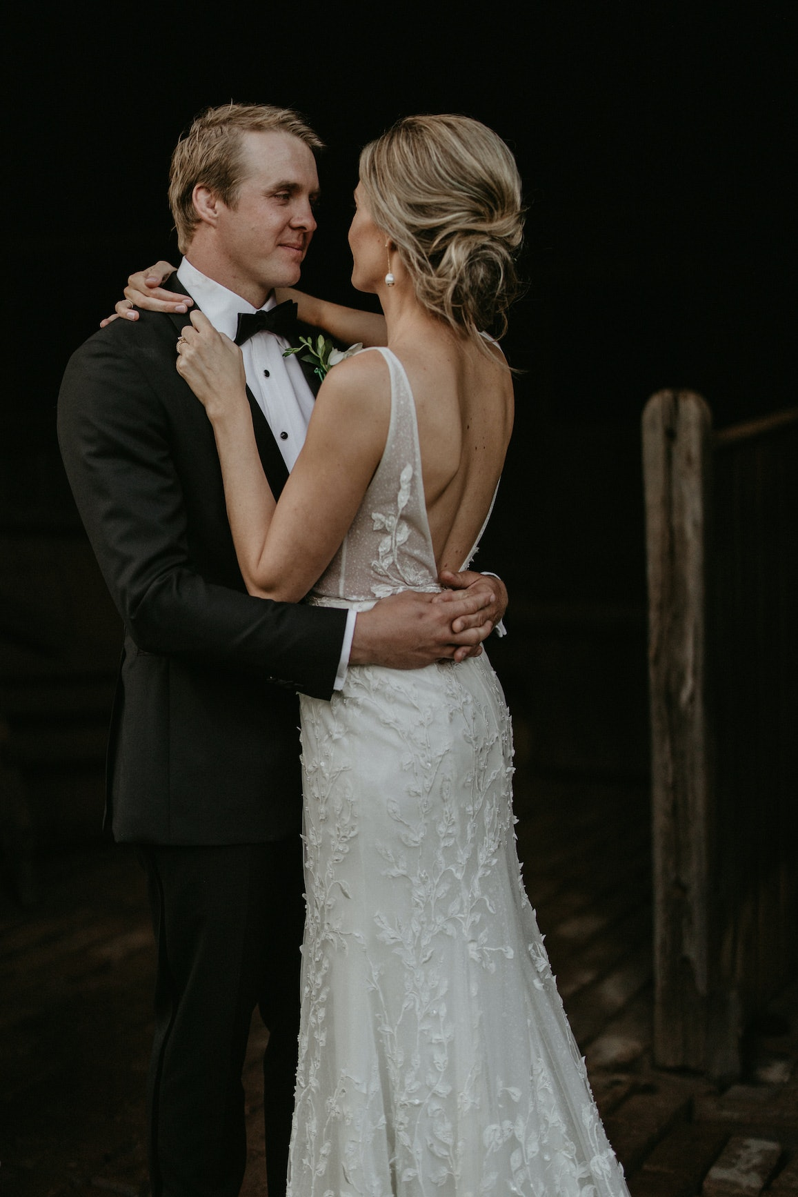 Bride and groom holding each other staring into each others eyes
