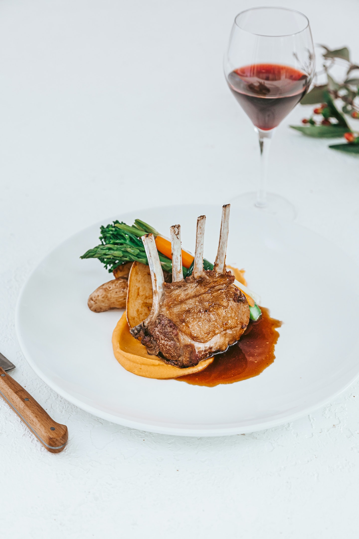 Lamb rack served on a plate with a glass of red wine