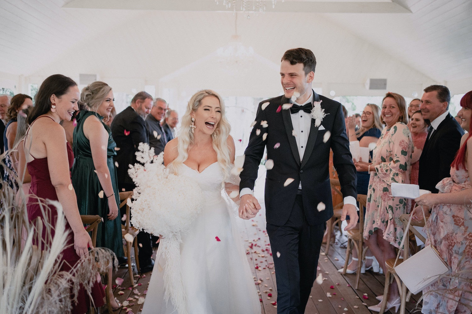 Bride and Groom hold hands laughing while walking down the aisle  scattered with rose petals