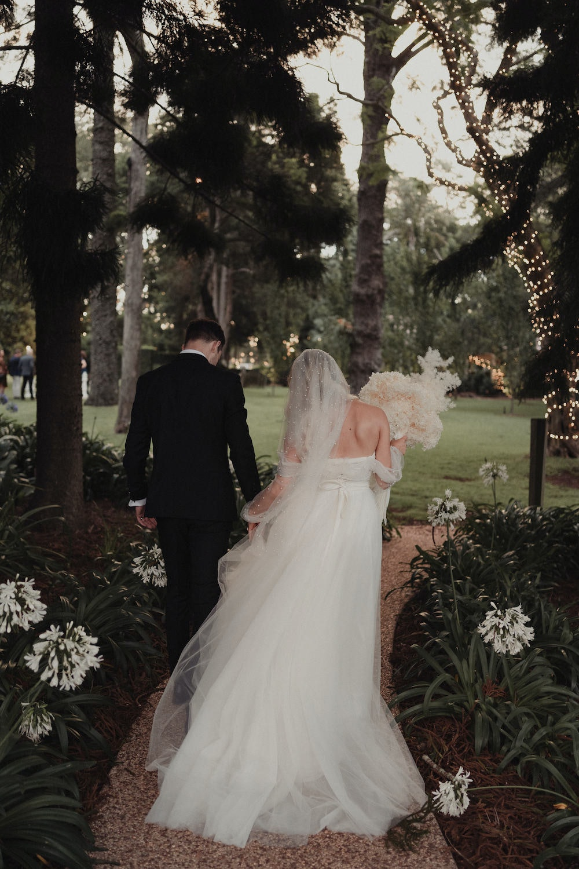 Bride and groom walking through gardens