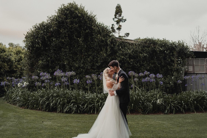 Bride and groom posing in gardens