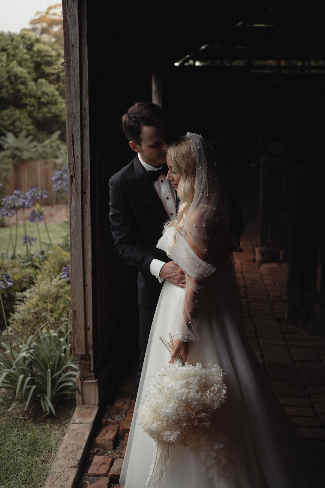Bride and groom posing in stables