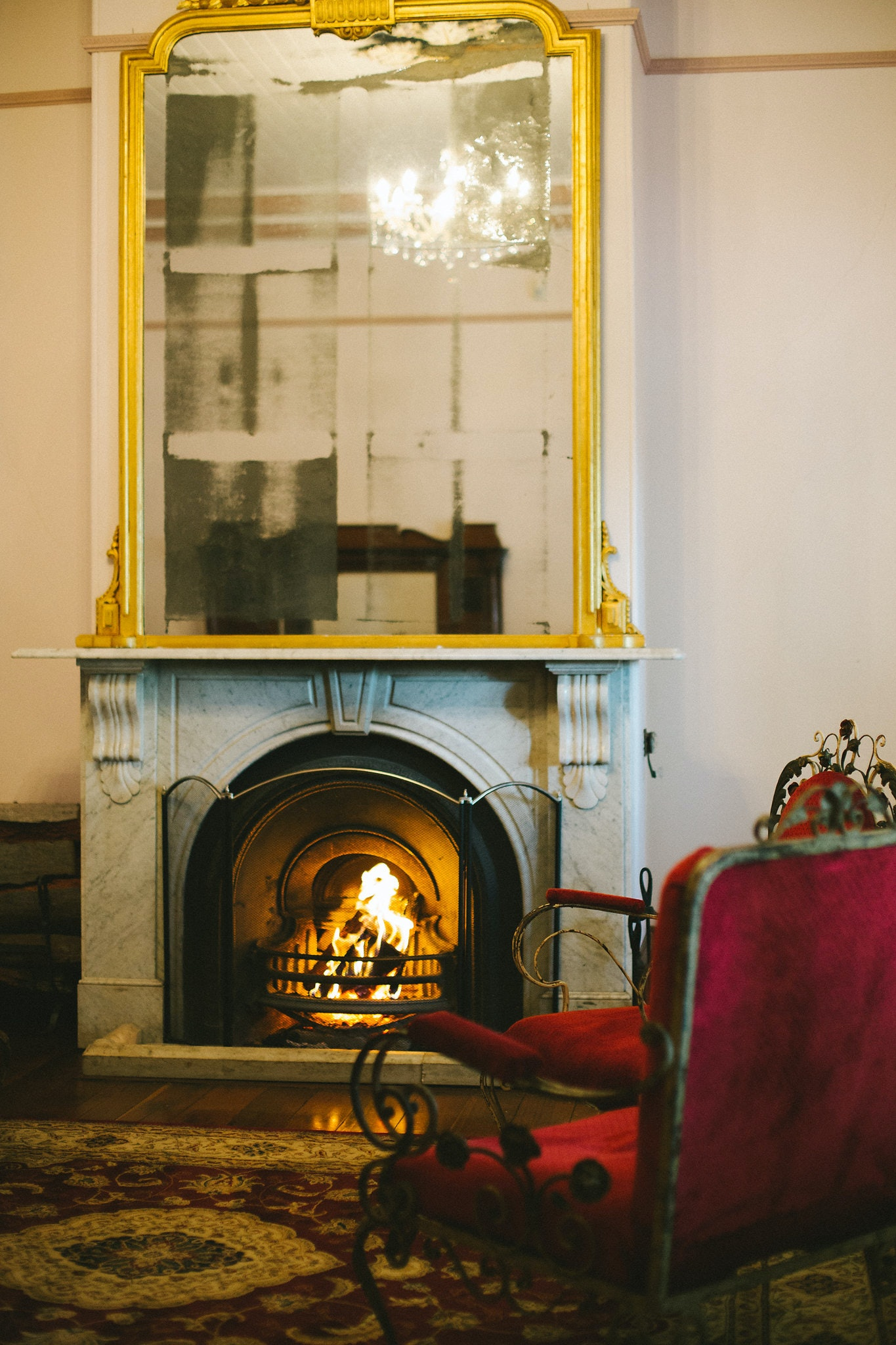 Marble fireplace with fire in historic homestead