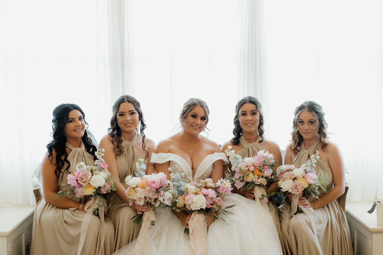 Bride and bridesmaid sitting on chaise lounge