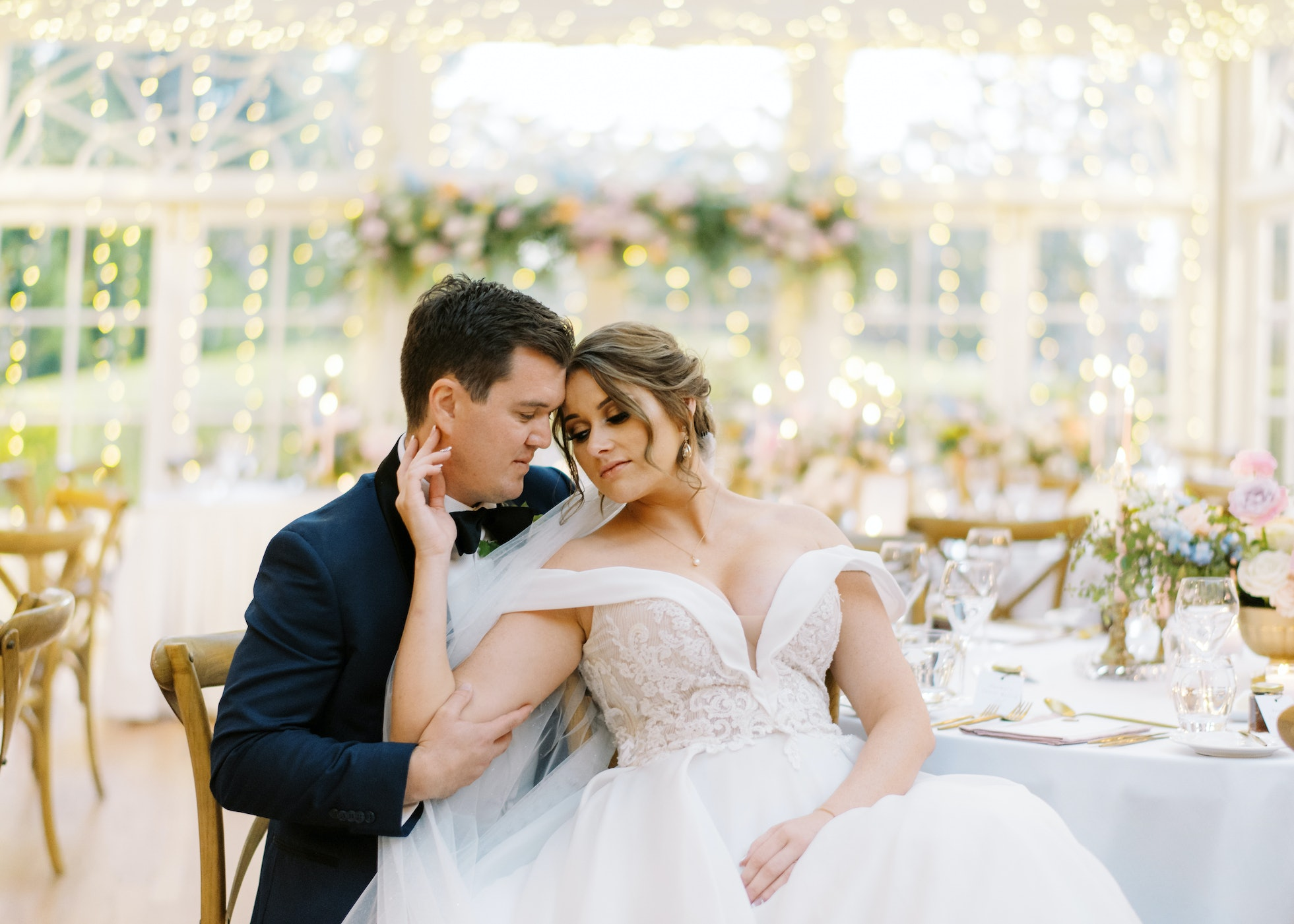 Bride and groom sitting on chairs together
