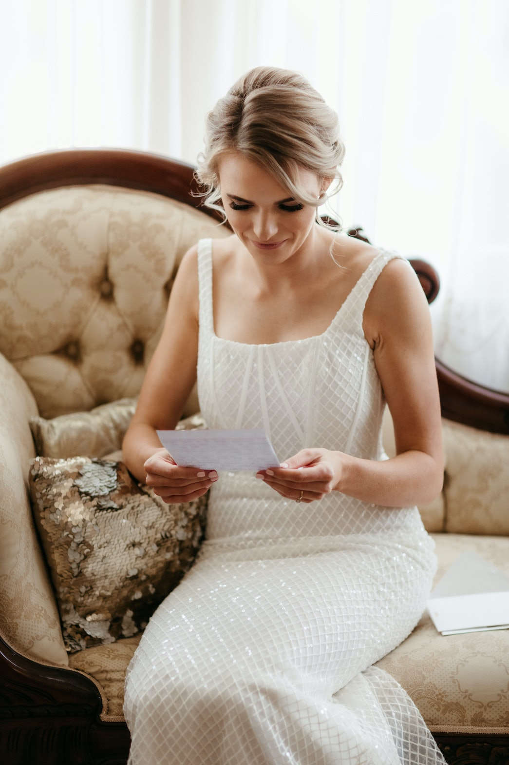 Bride reading a card from her groom on wedding day