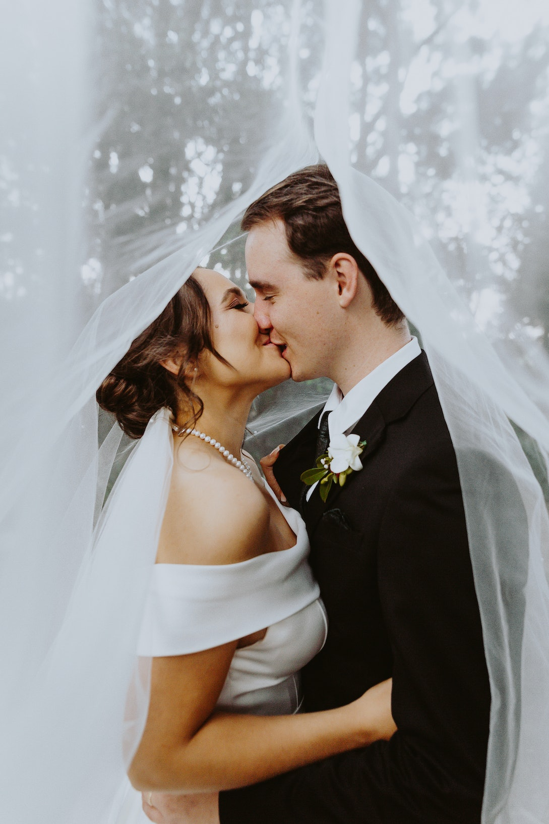 Bride and groom kissing under the brides veil