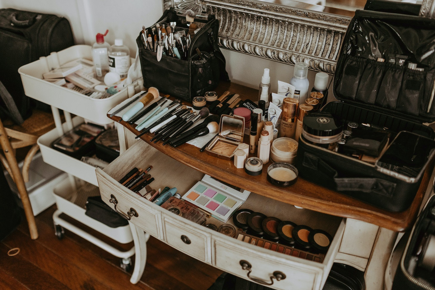 Console table covered with brushes, lipstick, and makeup