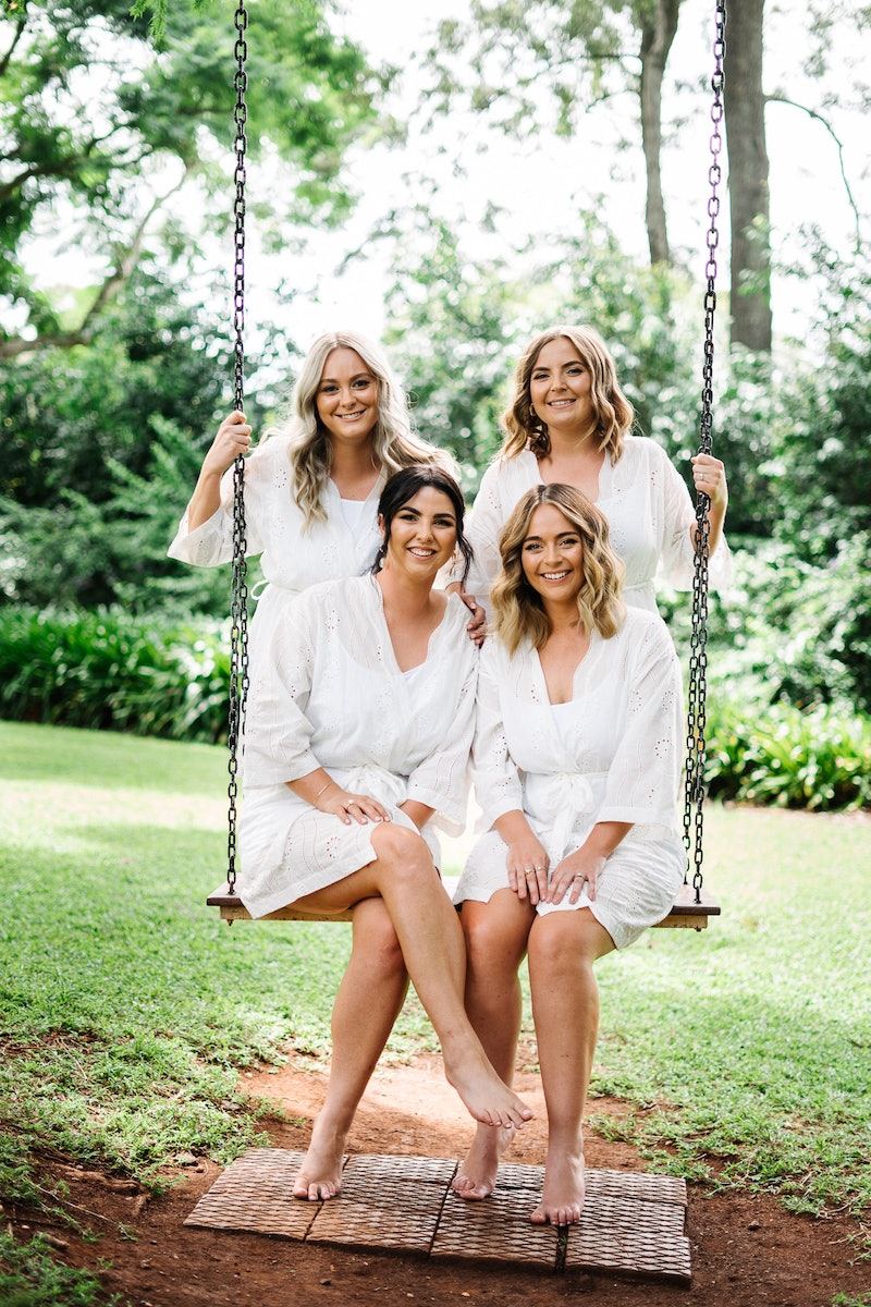 Bride and bridesmaids sitting on swing