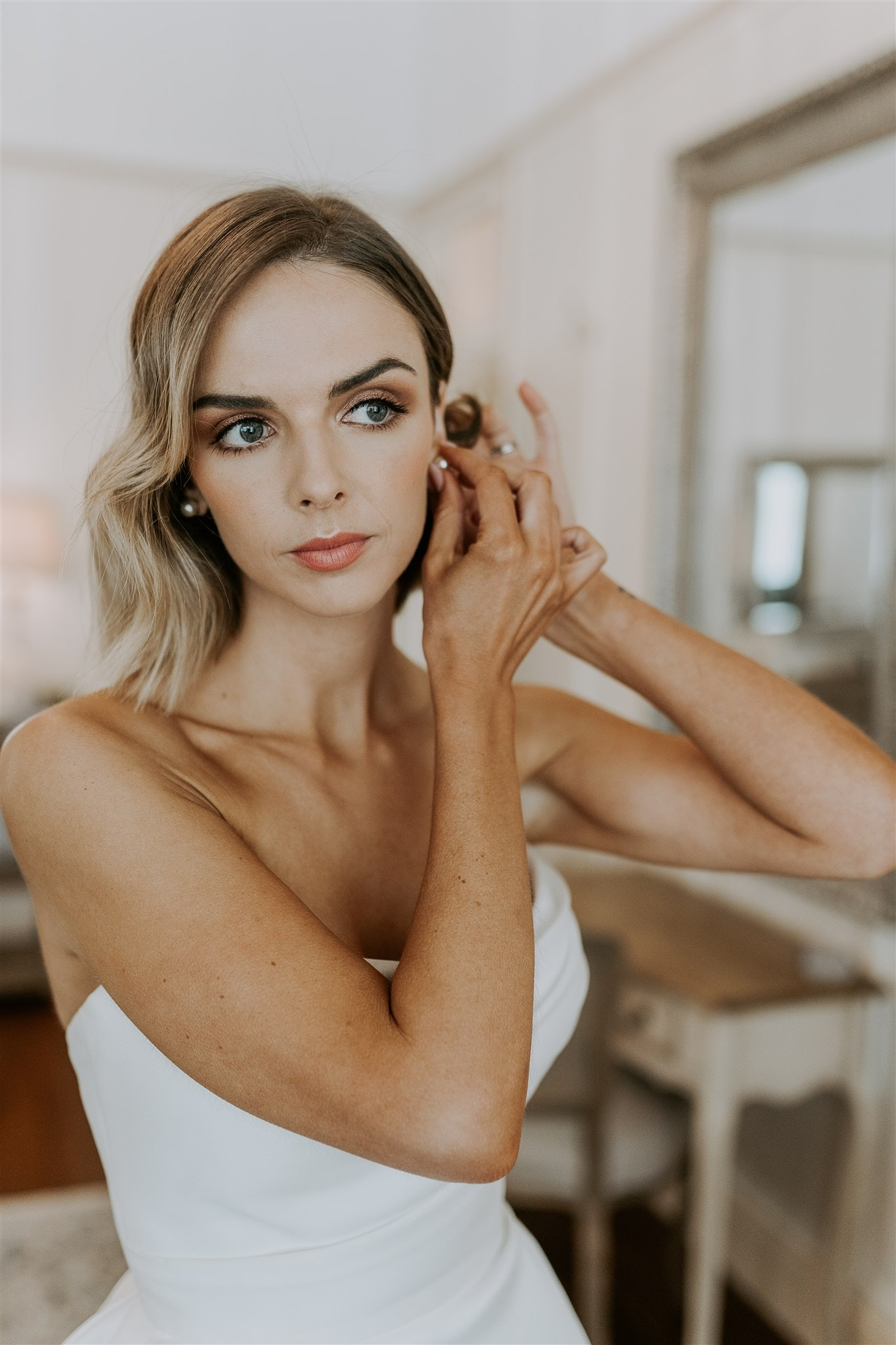Bride with  makeup on putting earrings in