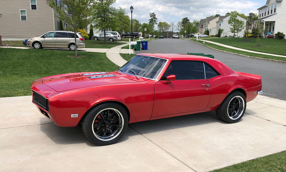 1968 Camaro Sport featuring Universal Pro Series Low Back seats with SPORT design including black vinyl and red contrast stitching. Paired with matching rear seat, door panels, and center console.