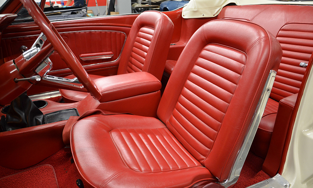 1965 Mustang featuring standard replacement bucket seats and rear seat in red. Includes matching standard door panels, carpet kit, and dash pad.