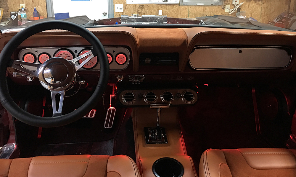 1965 Mustang featuring deluxe SPORT-R Pony seating with tan vinyl and suede. Includes matching dash pad, center console, door panels, rear seat, and trunk kit.