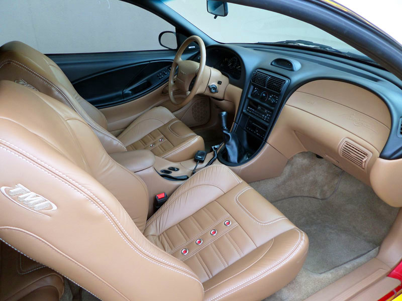 1995 Mustang featuring replacement SPORT-XR upholstery in tan vinyl with white contrast stitching, silver grommets, and red grommet backgrounds. Includes matching rear seat.