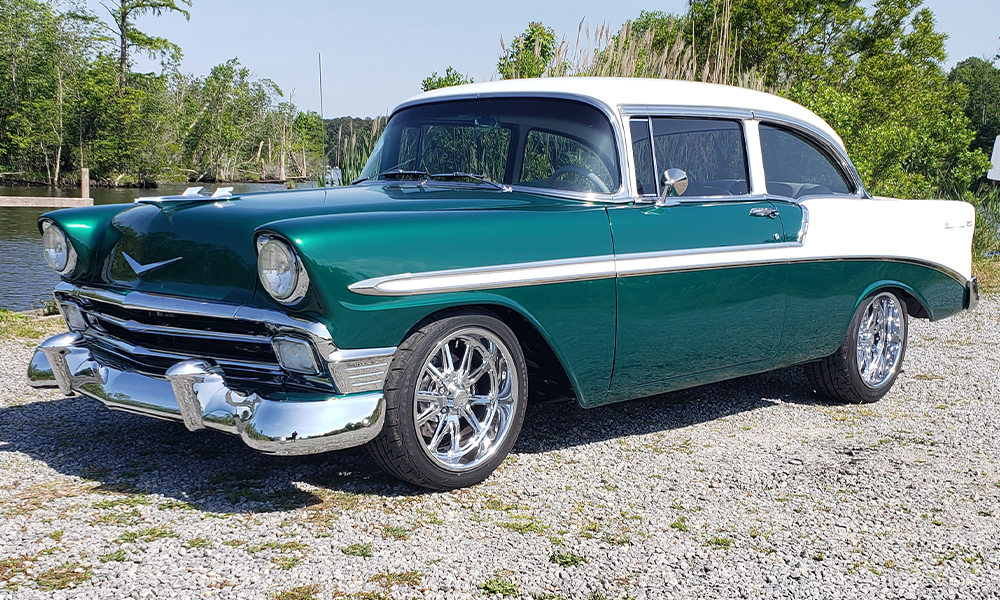 1956 Chevy Sedan featuring Universal Pro Grand seats in SPORT-X design with white vinyl, silver carbon vinyl, white contrast stitching, and silver grommets. Includes a matching rear seat with a waterfall console, center console, door panels, and carpet kit.