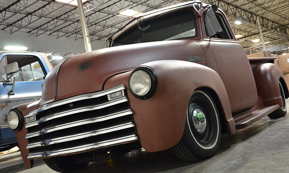 1954 Chevy Truck featuring Universal Pro Series bench in SPORT-XR design with saddle vinyl, whiskey suede, black accents, orange contrast stitching, and black grommets. Includes matching door panels.