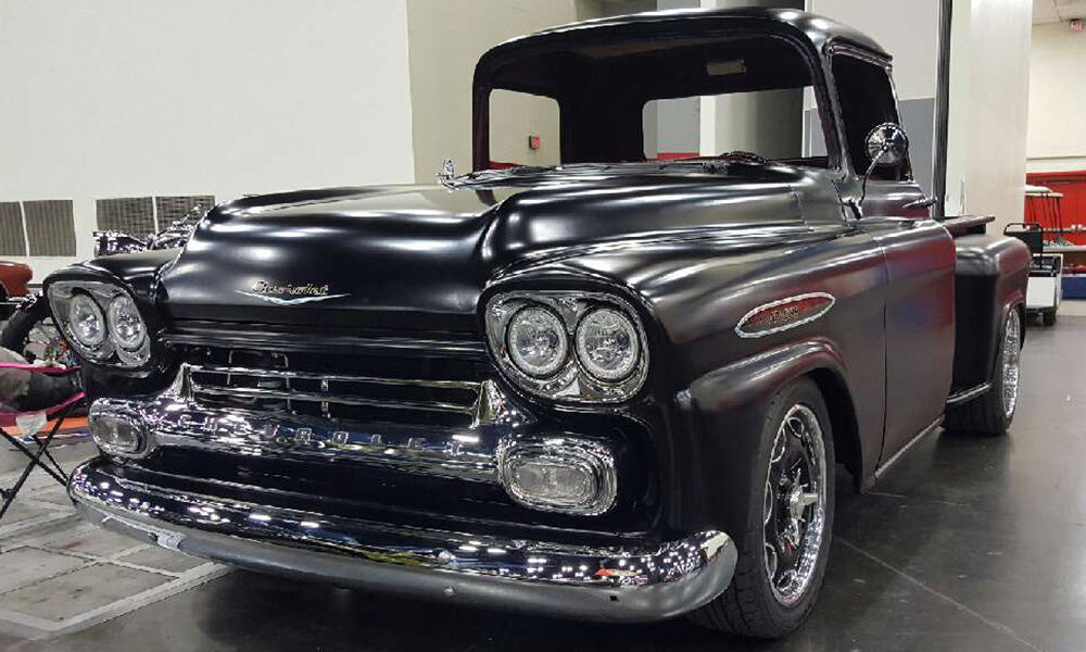 1959 Chevy Pickup featuring Universal Pro Series bench in SPORT-X design with red vinyl and mesh platinum vintage vinyl, black contrast stitching, and silver grommets. Includes matching door panels and console, and headliner.