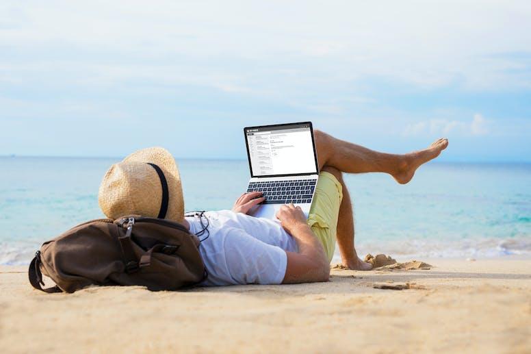 op het strand met MacBook