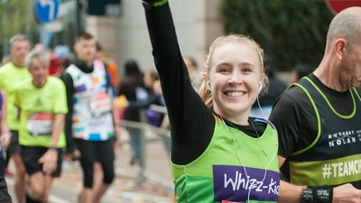 Smiling female running london marathon with Whizz Kidz vest