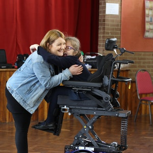 young girl in wheelchair hugging mother