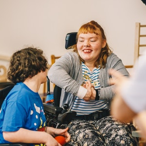 two young female wheelchair users smiling