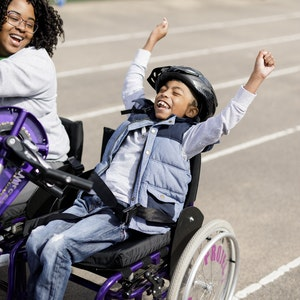young man smiling with hands up in wheelchair