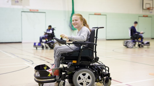 smiling young lady doing wheelchair sports