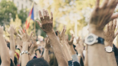 large group of people with arms up protesting