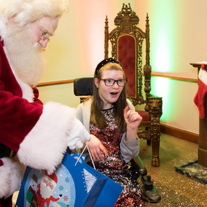young female wheelchair suer being visited by santa
