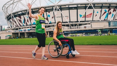 Young girl using a wheelchair alongside lady running around athletics track