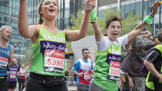 two ladies holding hands running London Marathon and cheering