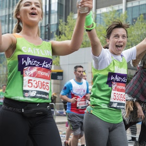 two ladies holding hands running London Marathon and cheering