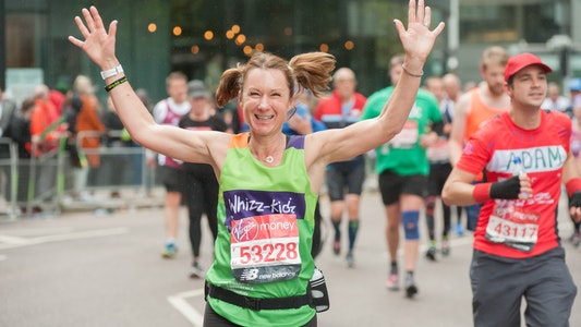 Women in pigtails with arms up in the air running London Marathon