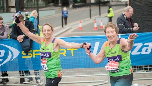 two older women holding hands running the London Marathon