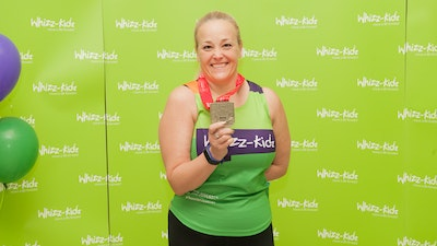 Woman smiling holding her London Marathon medal in front of green whizz-kidz branded board
