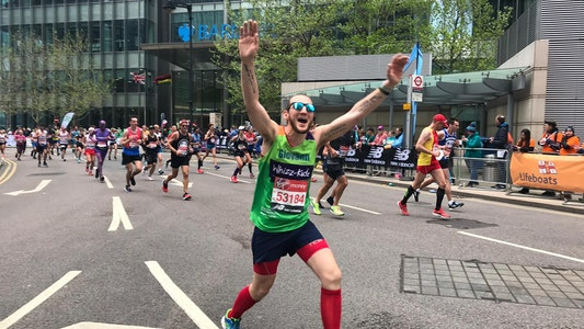 Man in sunglasses with his arms up running the London Marathon