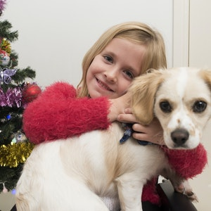 Young Wheelchair User Hugging Her Puppy