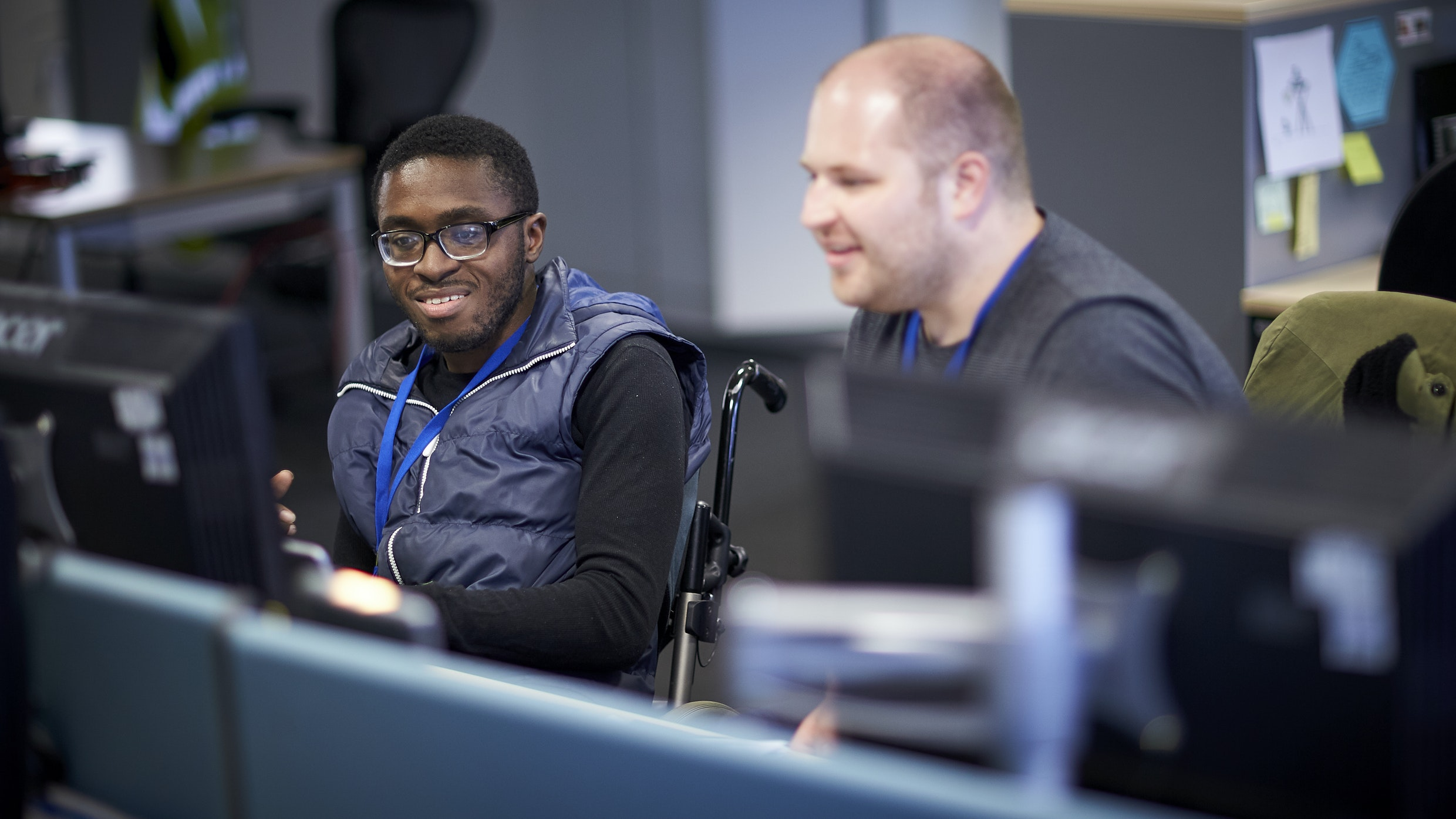 young wheelchair user in office environment with older colleague