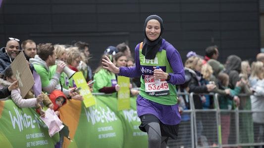 Whizz-Kidz runner running past charity cheer point