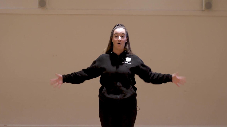 lauren looking at camera guiding dance classes in black