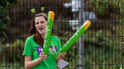 A woman dressed in green Whizz-Kidz merchandise and holding green Whizz-Kidz sticks, cheering on people out of frame