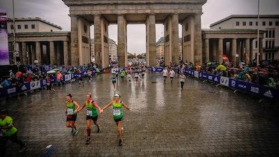 Three Women in Whizz-Kidz running vests run through Brandenberg Gate