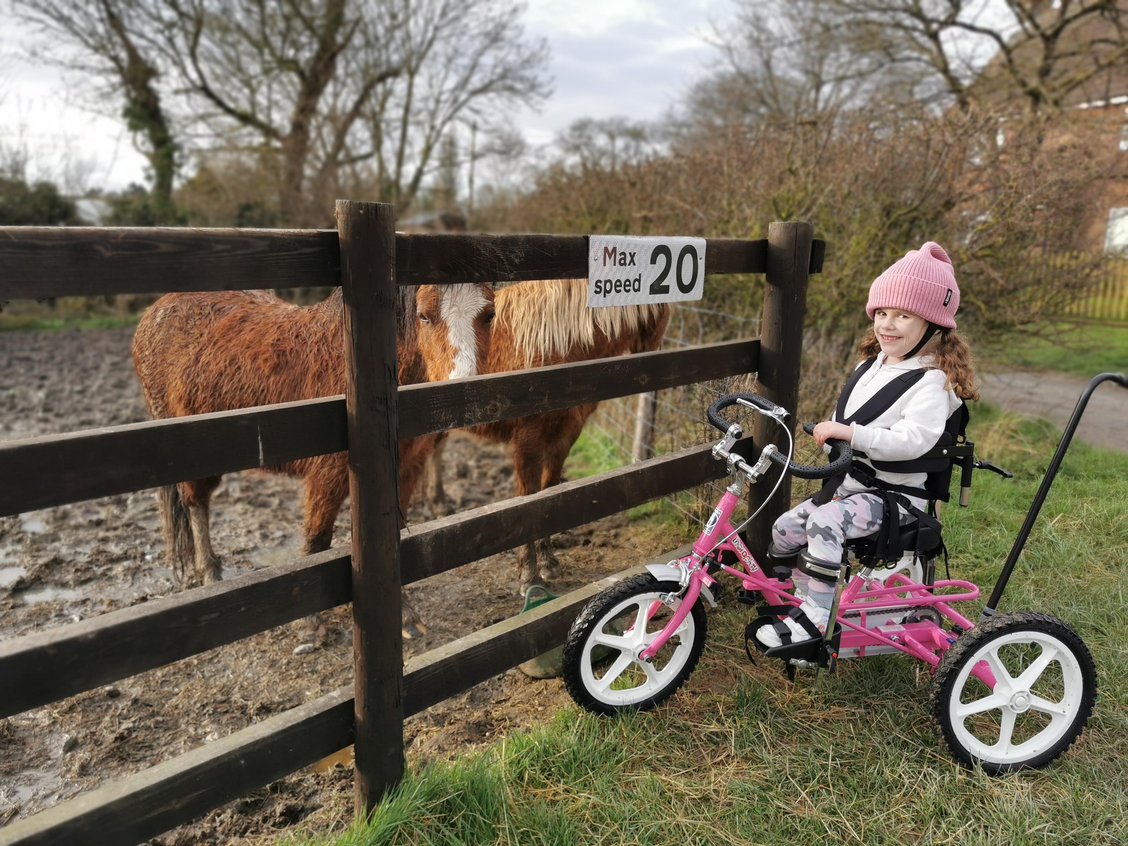 Carmela sming on her pink bike next to horses