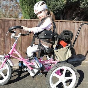 Carmela smiling on bike with black dog