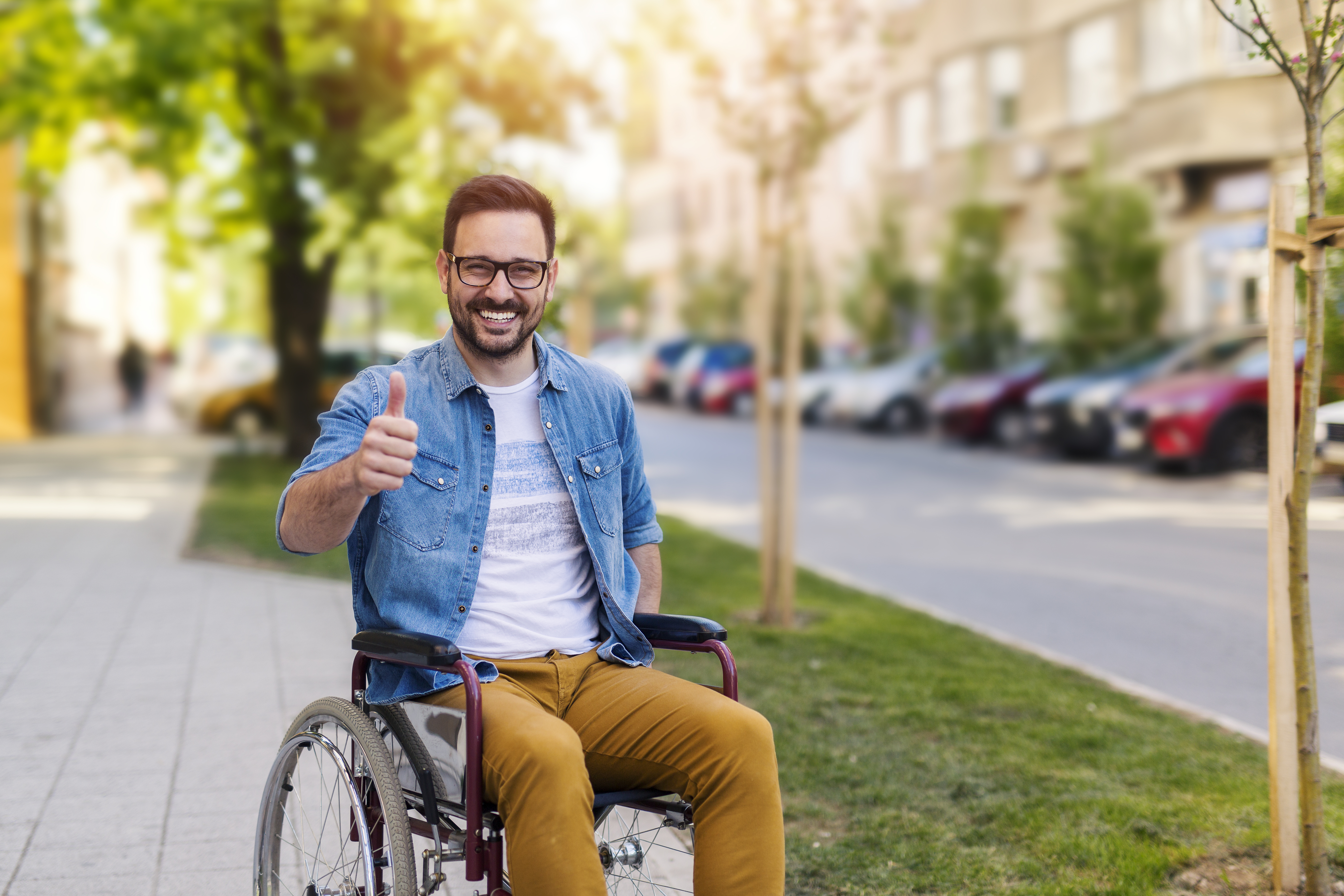 Stock image of a male wheelchair user smiling with a thumbs up