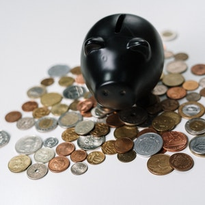 Black Piggy Bank with coins around it - photo by cottonbro