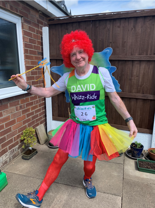 David poses in the tutu, wig and wand he ran the 2.6 challenge in