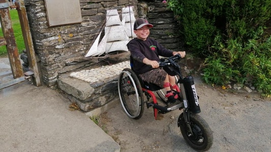 Harrison smiles in his Whizz-Kidz custom wheelchair