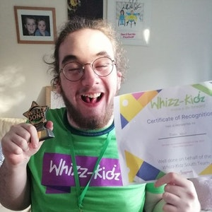 Owen holds up a certificate from Whizz-Kidz